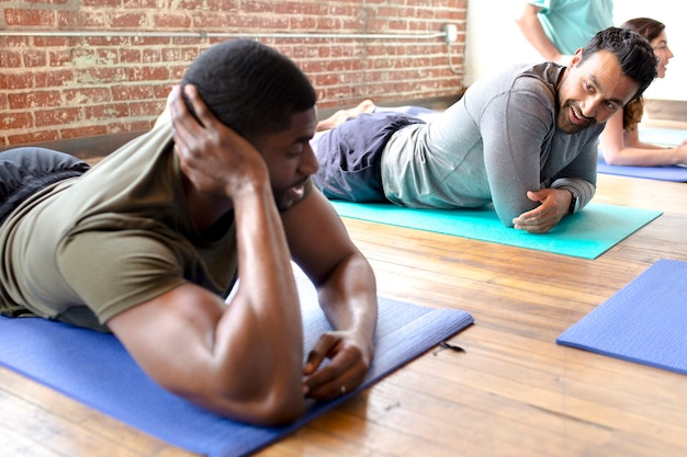 Sportive men relaxing on yoga mats