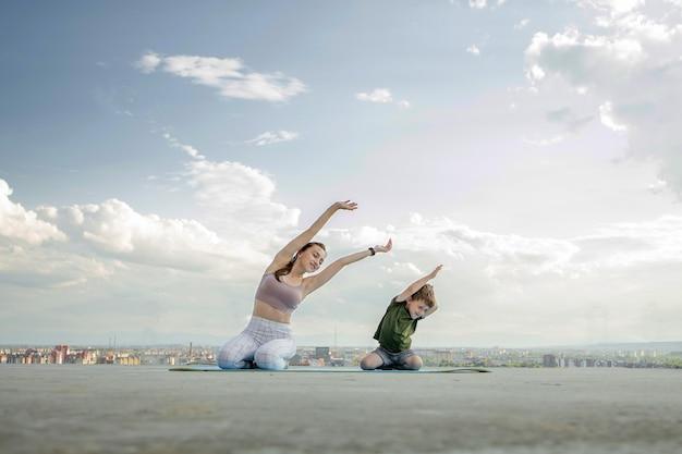 陽気な母親が幼い息子と一緒に運動をしている。スポーツ コンセプト。
