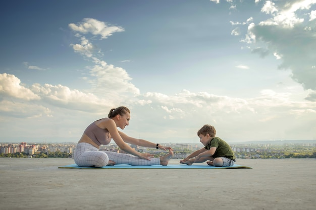 Sportive mother is doing workout with little son