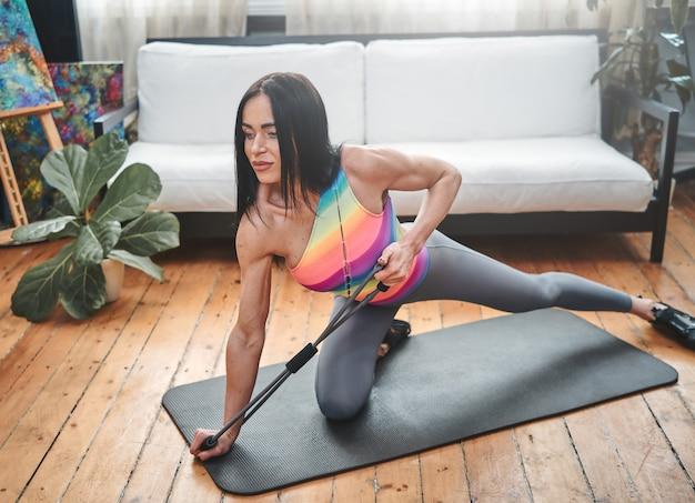 Спортивный портрет сильной спортсменки средних лет, тренирующейся с резиновыми резинками в светлой комнате с красивым интерьером.
