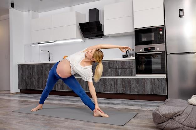 Спортивная беременная женщина делает уттита парсваконасану дома