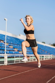 Sportive running woman training at stadium