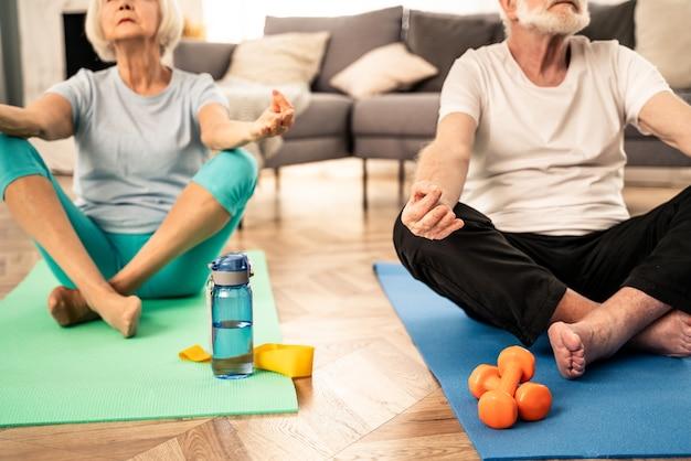 自宅でフィットネスとリラクゼーションのエクササイズをしているスポーティーな年配のカップル-健康と健康を維持するためのトレーニングをしている高齢者