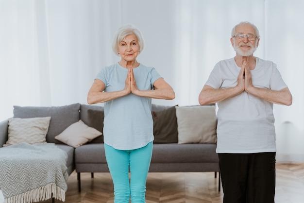 집에서 운동과 이완 운동을 하는 낚시를 좋아하는 노부부 - 건강하고 건강을 유지하기 위해 훈련하는 노인들