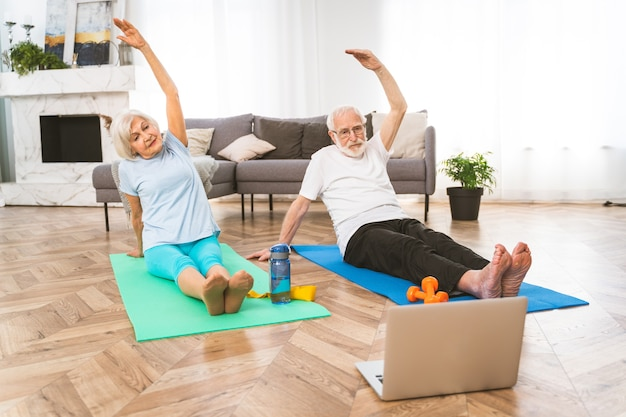 Sportive senior couple doing fitness and relaxation exercises at home - elderly people training to stay healthy and fit