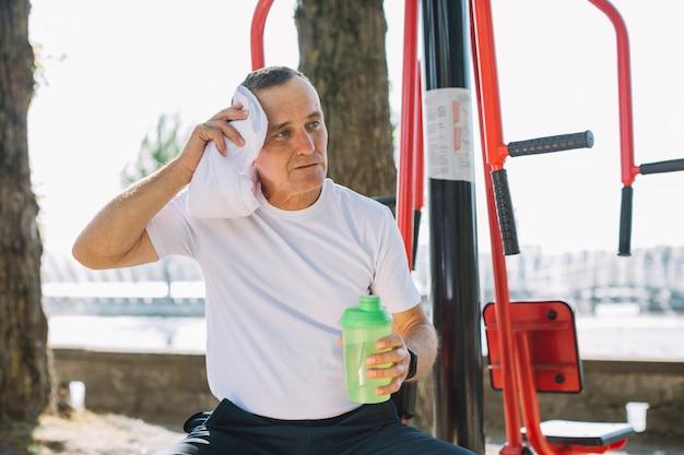 Sportive senior wiping perspiration