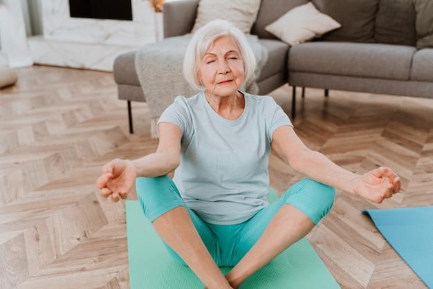 Спортивная старшая женщина, занимающаяся фитнесом и расслабляющими упражнениями дома - пожилые люди тренируются, чтобы оставаться здоровыми и подтянутыми