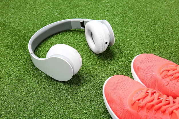 緑の芝生の上のスポーティな靴とヘッドフォン