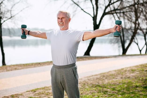 Спортивный дух. энергичный зрелый мужчина тренируется с гантелями и стоит в парке