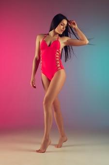 Фасонируйте портрет детенышей подходящей и sportive женщины в стильных розовых роскошных swimwear на градиенте. идеальное тело готово к летнему времени.
