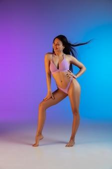 Фасонируйте портрет молодой подходящей и sportive женщины в стильных роскошных swimwear на градиенте. идеальное тело готово к летнему времени.