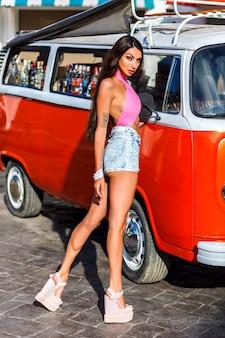 Donna abbronzata allegra in piedi in posa fiduciosa accanto al furgone vintage