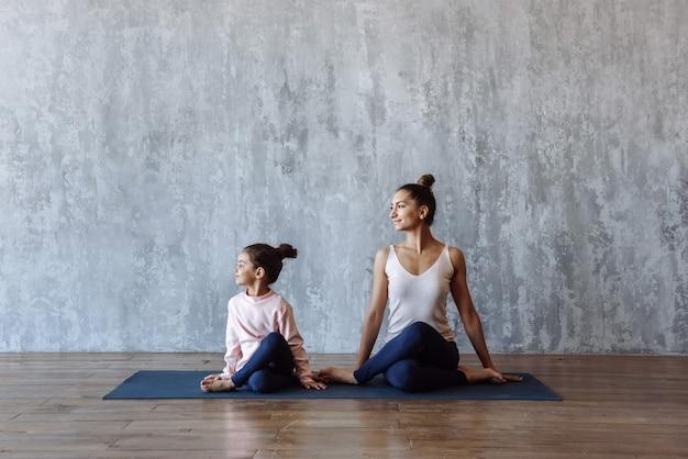 낚시를 좋아하는 여자와 그녀의 자식 소녀 요가 매트에 앉아 함께. 가족 스포츠