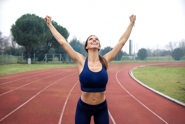 Sportive woman celebrating her satisfaction after running on the athletic field