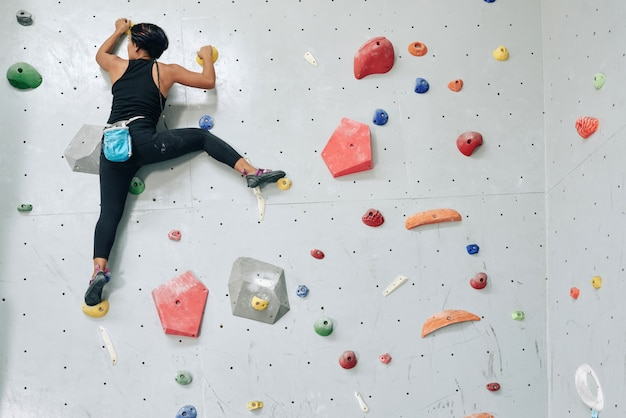 Sportive woman clambering wall in gym