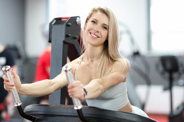 シミュレーターで上腕二頭筋のエクササイズをしているスポーティーな女性