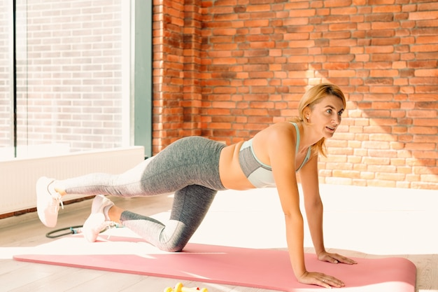 체육관 벽돌 벽에 매트에 운동을하는 낚시를 좋아하는 여자