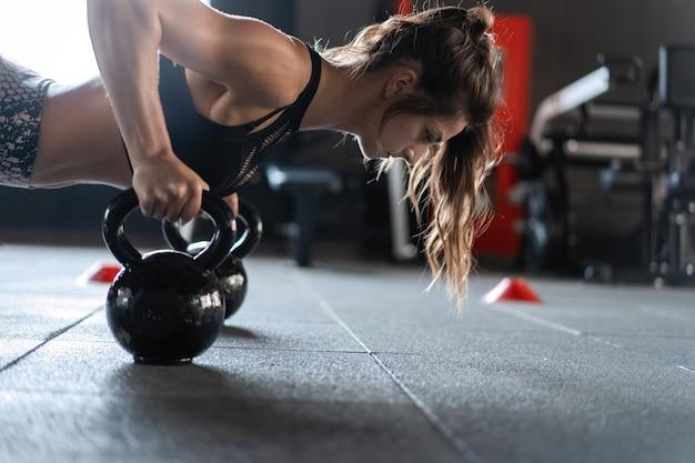 Kettlebells를 사용하여 체육관에서 팔 굽혀 펴기를하고 낚시를 좋아하는 여자