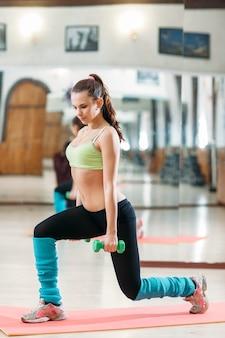 Спортивная женщина делает тренировку с гантелями