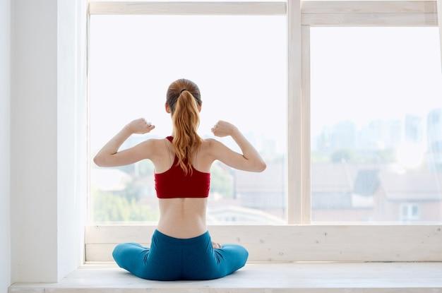 窓際でヨガエクササイズアーサナをしているスポーティーな女性。高品質の写真