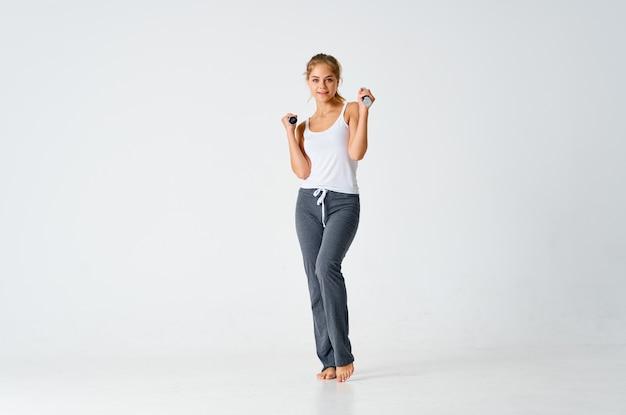 スポーツ女性のダンベルの筋肉は、フィットネスの動機を行使します