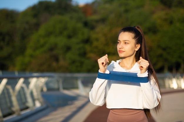 橋でフィットネスバンドで運動するスポーティーな女性。テキスト用の空き容量