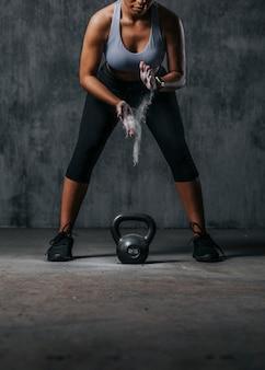 Спортивная женщина готовится поднять гирю