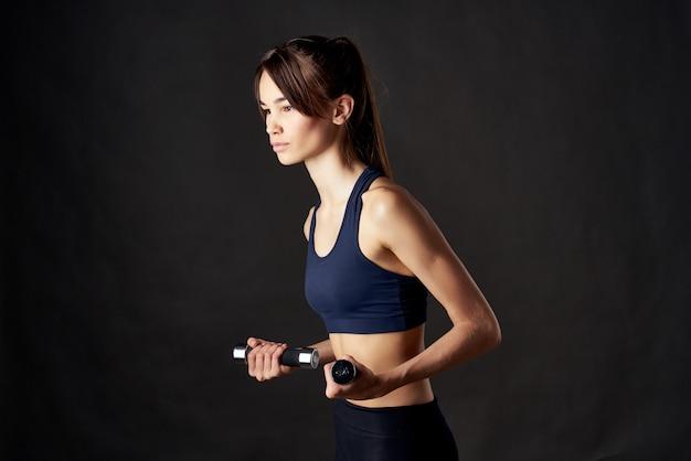 スリムな体型でダンベルトレーニングフィットネス運動を保持しているスポーティーな女性