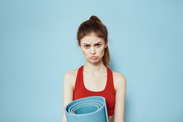 トレーニングエクササイズのための赤いタンクトップマットのスポーティーな女性