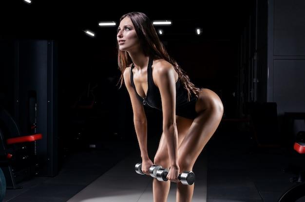 Спортивная женщина в тренажерном зале выполняет упражнение с гантелями. концепция фитнеса.