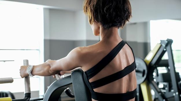 낚시를 좋아하는 여성이 블록 시뮬레이터에서 척추 근육 운동을 하고 있습니다. 체육관에서 스포츠 운동, 톤.