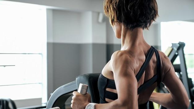 낚시를 좋아하는 여성이 블록 시뮬레이터에서 척추 근육 운동을 하고 있습니다. 톤.