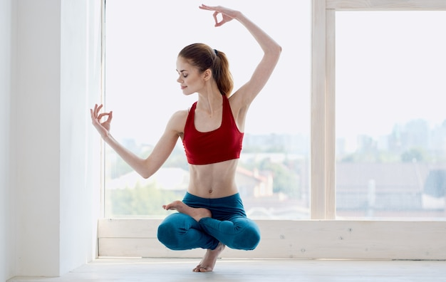 A sportive woman in jeans and a tank top practices yoga near the window. high quality photo