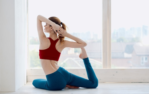 A sportive woman in jeans and a tank top practices yoga near the window