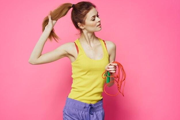 Спортивная женщина, прыгающая через скакалку, упражнения, желтая майка, розовое пространство.