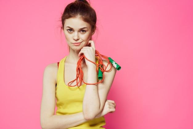 黄色のタンクトップピンクの手で縄跳び陽気な女性