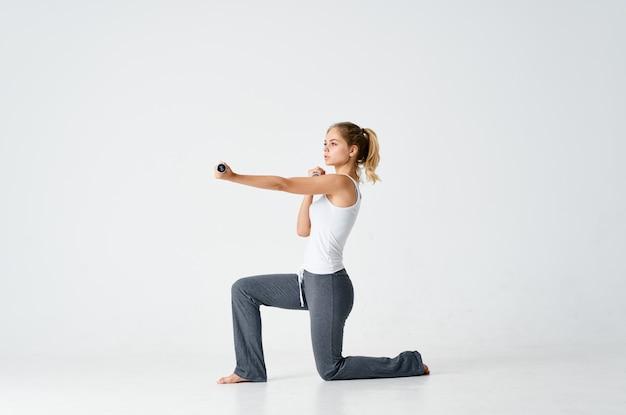 ダンベルでトレーニングモチベーション運動をひざまずくスポーティーな女性