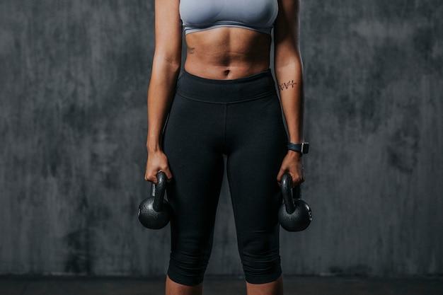 Спортивная женщина, поднимающая гири