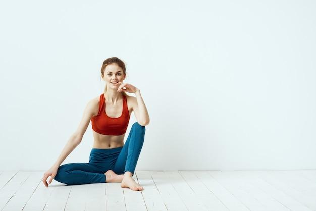 スポーティーな女性のポーズ体操バランス運動明るい背景。