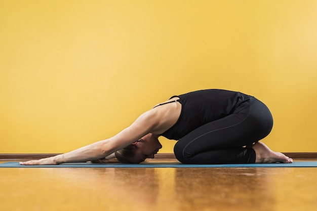 Sportive woman practicing yoga performs a balasana exercise a childs pose an athlete trains on a mat near a yellow wall in the studio