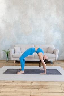 Спортивная женщина практикует йогу, растягивая дома на коврике, стоя в позе моста