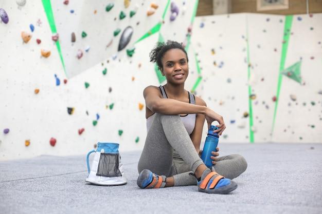 Спортивная женщина отдыхает после сеанса в альпинистском центре