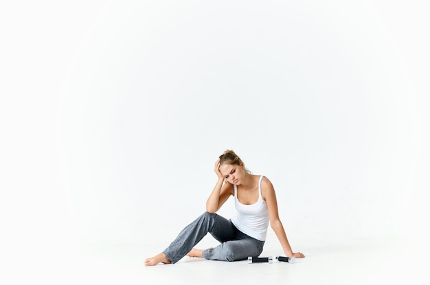 Sportive woman sitting on the floor with dumbbells muscles training arms