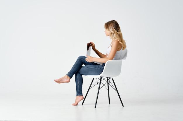 ノートパソコンの通信技術の前に椅子に座っているスポーティーな女性