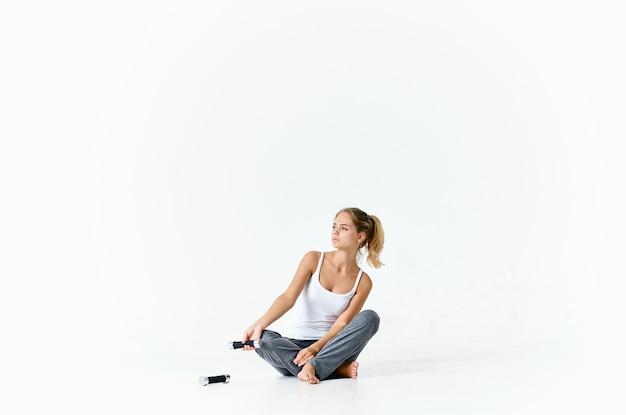 아령 운동 근육으로 바닥에 앉아 낚시를 좋아하는 여자
