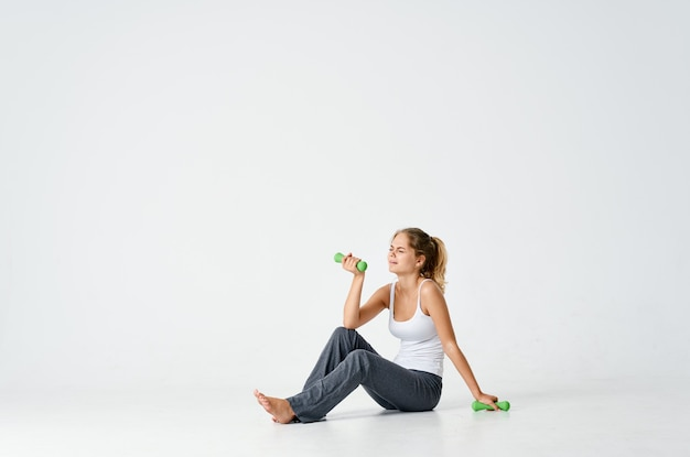 裸足のダンベルトレーニング運動の床に座っているスポーティーな女性