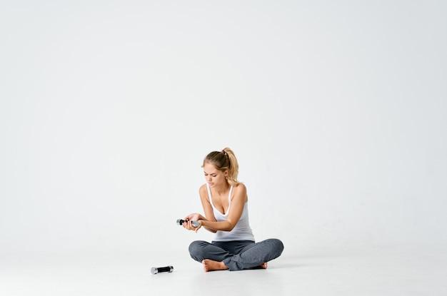 モチベーションエネルギー運動を充電する手で床ダンベルに座っているスポーティーな女性
