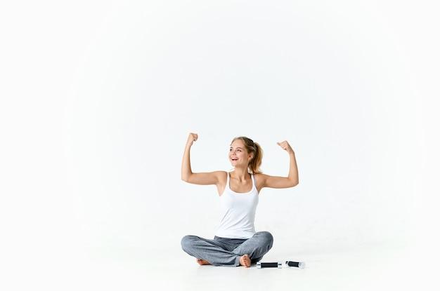 ダンベル筋肉トレーニング腕と床に座っているスポーティーな女性