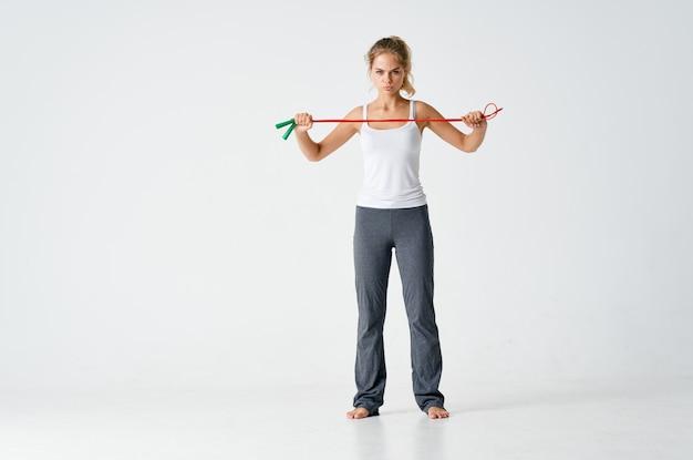手でロープをスキップするスポーティーな女性健康トレーニング孤立した背景