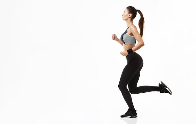 Sportive woman in sportswear training running on white.